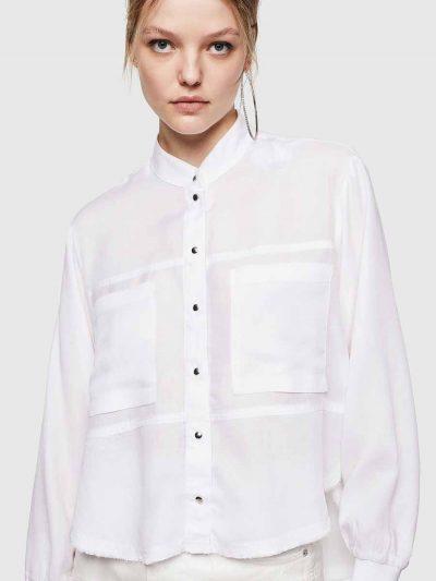 חולצה מכופתרת בצבע לבן, בסגירת כפתורי לחיצה ובגזרה משוחררת, קצרה מקדימה וארוכה מאחורה. בגב החולצה, כפתורים לחיצים לחשיפת הגב.