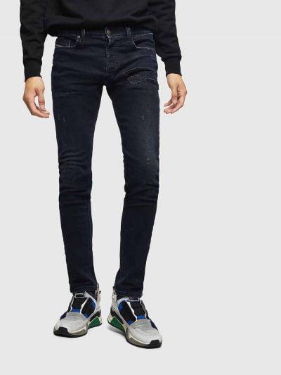 מכנסי ג'ינס בגזרת סלים (רחבה מעט בירכיים ונצמדת יותר עד הקרסול), בצבע כחול כהה בסגירת כפתורים. מתחת לכיס שמאל, בחלק העליון של הירך, קרעים מלבניים א-סימטריים, מקבילים זה לזה, סגורים עם פאץ' שחור למכנס שטיפה יחודית בחלקו הקדמי באזור האגן, הנותן אפקט תלת מימדי של