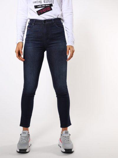 מכנס ג'ינס בגזרת מותן גבוהה, ישרה וצרה (באורך קרסול), בצבע כחול כהה קלאסי, בסגירת כפתורים. מכפלת הרגל רגילה. על החגורה מאחור, פאץ' עור עליו מוטבע