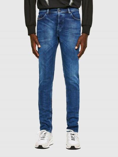 מכנסי ג'ינס בגזרת סלים(רחבה מעט בירכיים ונצמדת יותר עד הקרסול), בצבע כחול קלאסי, מעט משופשף, בסגירת כפתורים. על החגורה מאחור, פאץ' עור עליו מוטבע