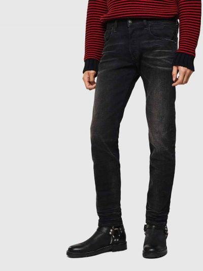 מכנסי ג'ינס בגזרה קלאסית ישרה, בצבע שחור משופשף, בסגירת כפתורים. על החגורה מאחור, תוית מתכת עם לוגו המותג.