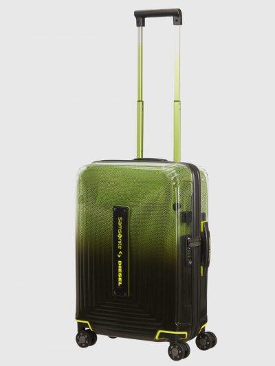 מזוודה בגזרת טרולי המתאימה לעליה למטוס, בצבע ירוק/שחור/צהוב, חלקה העליון שקוף למחצה והתחתון אטום. המזוודה היא חלק מקולקציית שיתוף הפעולה האייקוני