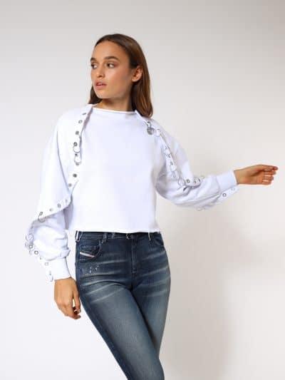 סווטשרט בצבע לבן בגזרה רחבה ובמראה של שכמיה. לולאות מתכת דו צדדיות לאורך השרוולים.