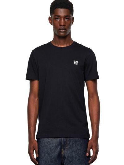 טישרט חלקה שרוול קצר, בגזרה צרה בצבע שחור, עשויה כותנה. על החזה משמאל, מוצמד פאץ' מרובע קטן, עשוי מיקרופייבר, הנושא את לוגו המותג.