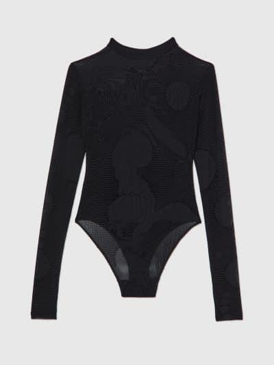 בגד גוף שחור העשוי בד רשת דק ,מעוטר ברקמת נקודות בחלקו הקדמי. לפריט שרוולים ארוכים במיוחד וצווארון עגול ונסגר בכפתורים בחלקו התחתון.