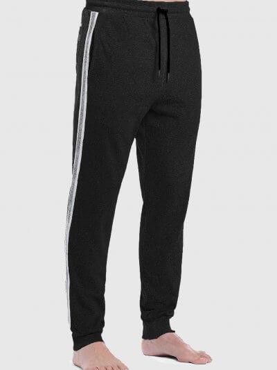 מכנסי טרנינג, בצבע שחור, בגזרה רגילה, עם חגורת מותן אלסטית ושרוכים עם סיומת מתכתית. שני כיסים קדמיים ופסים ממותגים לאורך הרגליים.