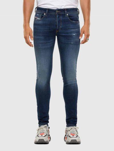 מכנסי ג'ינס בגזרת סקיני (צמודים לכל אורך הרגל) ונמוך, בצבע כחול, בסגירת כפתורים, עשוי מבד ג'ינס אלסטי. על ירך ימין בצד, קרעים קטנים סגורים ובצד הכיס השמאלי הקדמי וכן על שולי הכיסים האחוריים, שפשופים קלים. על החגורה מאחור, פאץ' עור עליו מוטבע לוגו המותג.