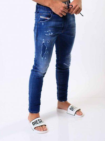 מכנס ג'וג בגזרה צרה, בצבע כחול משופשף עם חגורת גומי אלסטית ושרוך.