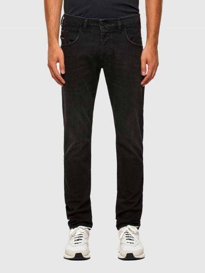 מכנסי ג'ינס בגזרה קלאסית ישרה, בצבע שחור, בסגירת כפתורים. על החגורה מאחור, תוית מתכת עם לוגו המותג.