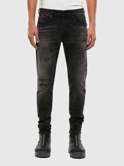 מכנסי ג'ינס בגזרה צרה וישרה (סלים פיט), בצבע אפור כהה, בסגירת רוכסן. ברגל ימין, על הברך והירך, קרעים סגורים בטלאי שחור תפורים בצבעי הרקע. על ירך שמאל, קרעים נוספים בגדלים שונים, סגורים גם הם. על הכיס האחורי הימני, רקמת הלוגו ועל החגורה מאחור, פאץ' עור עליו מוטבע לוגו המותג.