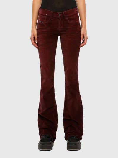 מכנס ג'ינס בגזרת מותן נמוכה, מתרחב (צמוד על הירך, מתרחב מהברך מטה), בצבע בורדו/יין, בסגירת רוכסן. הג׳ינס מעושר באפקט קטיפה ושיפשופים בעובדת יד לה