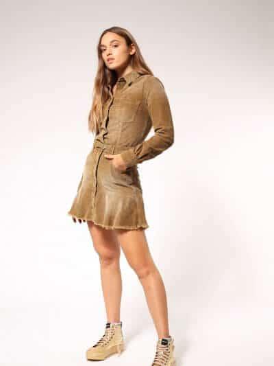 שמלת קורדרוי בצבע קאמל בשטיפת וינטג׳ ובגזרת מיני עם קצוות פרומים. השמלה במראה של חצאית וחולצה מחוברים, נסגרת בכפתורי לחיצה וכוללת חגורת מותן דקה