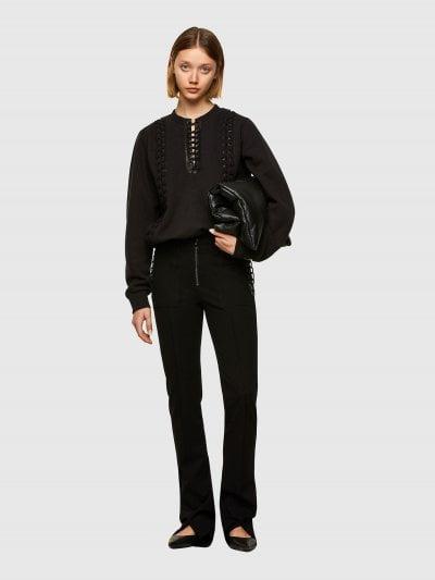 מכנסיים בצבע שחור, הנסגרים ברוכסן, בגזרת ׳פלייר׳ צרה ומתרחבת במעט ברגליים, עשויים מבד ויסקוזה עם סטרץ׳. בצדדים עיטורי שרוכים ועור ושני כיסים גדול