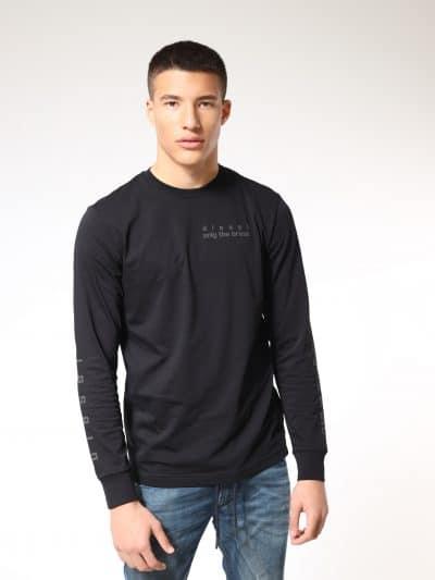 טישרט שרוול ארוך, בגזרה צרה בצבע שחור, עשויה כותנת ג'רזי משובחת. על החזה משמאל, על הגב ועל השרוולים, הדפסי פלסטיסול מבריק, בצבע הרקע