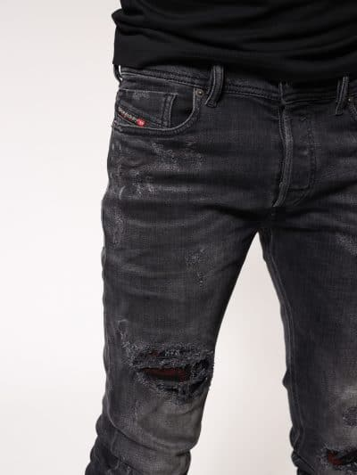 מכנסי ג'ינס בגזרת סקיני (צמודים לכל אורך הרגל) ונמוך, בצבע אפור/שחור משופשף, בסגירת רוכסן, עשוי מבד ג'ינס אלסטי. על ירך ימין, קרע מאוזן, סגור בפא