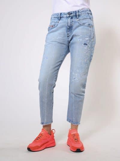 מכנס ג'ינס בגזרת מותן רגילה, בויפרנד (צללית מעט מרושלת, סיומת רגל מעוקלת שמצטמצמת על הקרסול), בצבע תכלת, בסגירת רוכסן. למכנס, עיטור של תפרי מכפלת