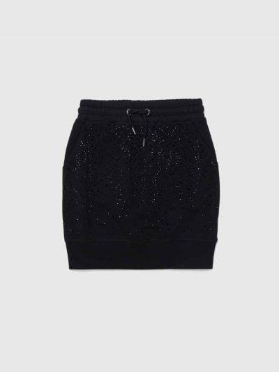 חצאית כותנה בצבע שחור, בגזרה רגילה, עם חגורת מותן מגומי ושרוכים עם סיומת מתכתית. החצאית משובצת במיקרו-ניטים בצבע שחור מבריק ושני כיסים קדמיים. פאץ׳ לוגו המותג מאחורה, בצבע הרקע.
