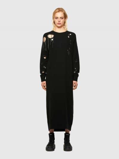 שמלת סריג מקסי, בצבע שחור, עם שרוולים אורכים ובגזרה רחבה. לאורך השמלה, עיטורים עגולים הנגזרו ביד ורקומים בשרשרת מתכתית. על העורף, פאץ' לוגו המותג