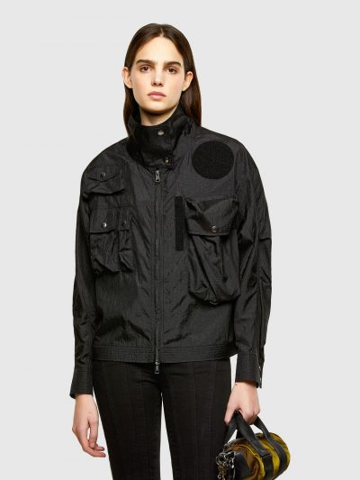 ג׳קט ניילון בצבע שחור עם צווארון מוגבה בגזרה משוחררת ובסגירת רוכסן דו כיווני. השרוולים ניתנים להידוק באמצעות כפתורי לחיצה. על הגב חגורה להידוק הג
