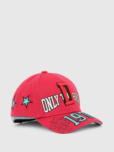 כובע מצחיה בצבע אדום עשוי מכותנת טוויל רכה ובמראה של שני כובעים תקועים יחד כאשר התחתון הוא כובע ג'ינס כחול. על החלק העליון פאצ'ים ורקמות צבעוניות
