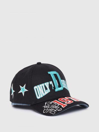 כובע מצחיה בצבע שחור עשוי מכותנת טוויל רכה ובמראה של שני כובעים תקועים יחד כאשר התחתון הוא כובע ג'ינס כחול. על החלק העליון פאצ'ים ורקמות צבעוניות