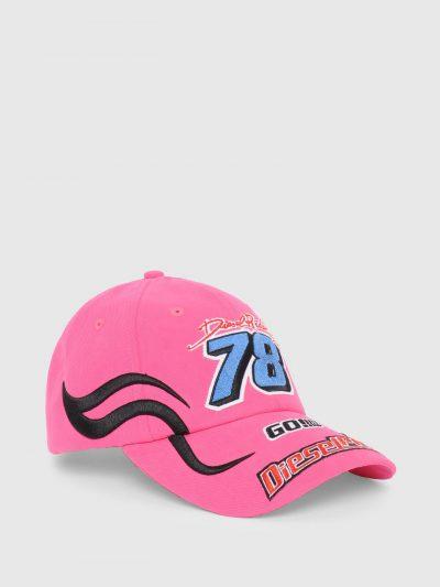 כובע מצחיה בצבע ורוד עשוי מכותנת טוויל רכה. על הכובע כיתובי לוגו צבעוניים רקומים בתלת מימד בהשראת רוכב מירוץ.