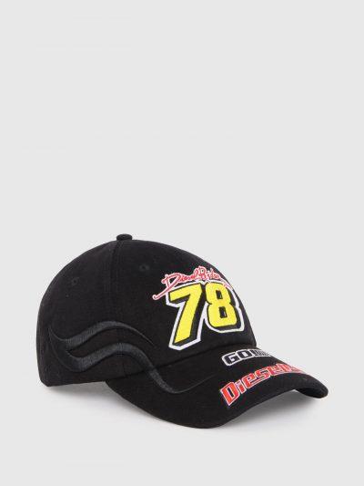 כובע מצחיה בצבע שחור עשוי מכותנת טוויל רכה. על הכובע כיתובי לוגו צבעוניים רקומים בתלת מימד בהשראת רוכב מירוץ.