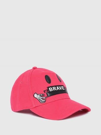 כובע מצחיה בצבע ורוד עם פאצ'ים ורקמה בצבע שחור של לוגו וסלוגן המותג, במראה סמיילי.