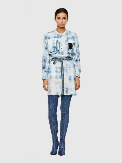 שמלה בגזרה רגילה עם הדפס משובץ בצבע כחול ואפקט ג'ינס מולבן. השמלה נסגרת בכפתורי לחיצה. השמלה מעוטרת ברצועות ג'ינס במותן ולאורך הכפתורים. מקדימה ש