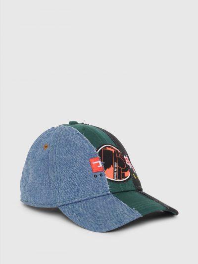 כובע מצחיה עשוי מכותנת טוויל רכה וג'ינס. הכובע במראה של שילוב של שלושה כובעים שונים ובצבעים של שחור, ירוק וג'ינס כחול. מקדימה פאצ'ים ורקמה שונים