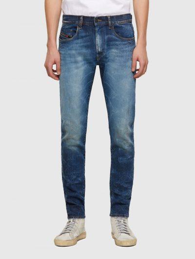 מכנסי ג'ינס בגזרה צרה וישרה (סלים פיט) בצבע כחול משופשף בסגירת רוכסן. על הכיס האחורי הימני רקמת האות D ועל החגורה מאחור פאץ' עור גדול עליו מוטבע