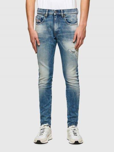מכנסי ג'ינס בגזרה צרה וישרה (סלים פיט), בצבע כחול, בסגירת רוכסן. שטיפת המכנס, כוללת אפקטים וניואנסים בברכיים, בכיסים ובתפרים. על הכיס השמאל בצד ה