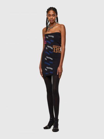 שמלת מיני בצבע שחור בגזרת סטרפלס צרה ומבד סריג. המכפלת התחתונה חתוכה בצורה א-סימטרית ולוגו המותג בצבעים שונים והדפסים שונים לכל אורך השמלה.