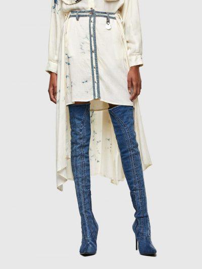 חצאית בצבע שמנת בגזרה רגילה עם הדפס משובץ בצבע כחול ואפקט ג'ינס מולבן. החצאית נסגרת בכפתורי לחיצה וכוללת שכבה אחורית ארוכה יותר המדמה חולצה עם שר