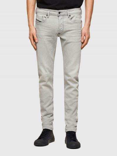 מכנסי ג'ינס בגזרת סקיני (צמודים לכל אורך הרגל) ונמוך, בצבע אפור בהיר, בסגירת כפתורים, עשוי מבד ג'ינס אלסטי. על החגורה מאחור, פאץ' עור עליו מוטבע
