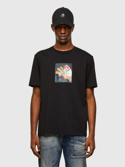 טישרט שרוול קצר בגזרה רגילה בצבע שחור עשויה כותנת ג'רזי משובח. על החזה הדפס מרובע דמוי תמונה של יד עם ציפורניים בצבע טורקיז המקמטת תוית לוגו המות