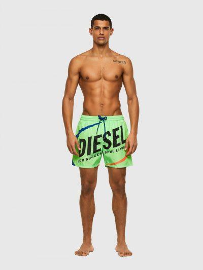 בגד ים אורך בינוני בצבע ירוק וחגורת מותן אלסטית עם שרוכים כחולים וסיומת מתכתית. מקדימה הדפס לוגו גדול בצבע שחור עם הדפס כתום וכחול. כיס אחורי הנס