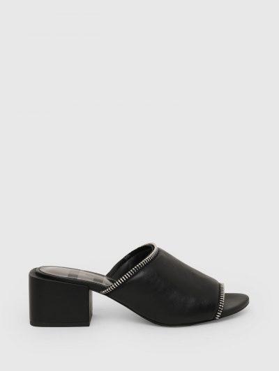 נעלי עור בצבע שחור עם עקב מרובע ורצועה מרופדת רחבה עם סיומת רוכסן. שם המותג על המדרס.