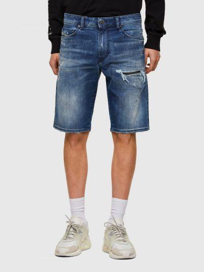 ברמודת ג'ינס באורך הברך בצבע כחול בסגירת רוכסן. על ירך שמאל מעל הברך קרע אנכי סגור. באזור המפשעה שפשופים מאוזנים למראה תלת מימדי לבוש ומספר שריטו