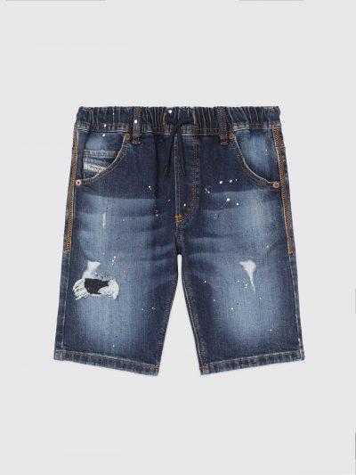 מכנס ברמודה לילדים בצבע כחול משופשף, על רגליים ימין ושמאל קרעים סגורים בפאץ' והתזות צבע. עשוי מבד ג'וג ג'ינס המשלב תפירה בצורת שתי וערב של שני סו