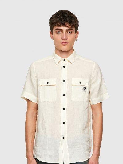 חולצה מכופתרת בצבע קרם מבד פשתן בסגירת כפתורים עם שרוולים קצרים ובגזרה רגילה. שני כיסים בחזה הנסגרים בכפתור ופאץ' 'מוהוק' על כיס שמאל.