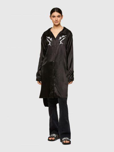 שמלה בגזרה רחבה במראה של חולצה מכופתרת בצבע שחור מסאטן. לשמלה סגירה קידמית של כפתורי לחיצה כסופים ועיטורי רקמה צבעוניים. לשרוולים רצועות המאפשרות