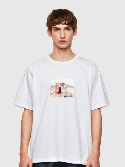 חולצת טי, שרוולים קצרים, צבע לבן, הדפס מקדימה של צילום צריף על חוף ים
