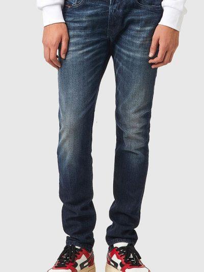 מכנסי ג'ינס בגזרת סקיני (צמודים לכל אורך הרגל) ונמוך, בצבע כחול כהה בסגירת כפתורים, עשוי מבד ג'ינס אלסטי. על החגורה מאחור, פאץ' עור עליו מוטבע לו